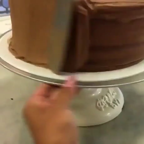 Deftly frosting a chocolate cake