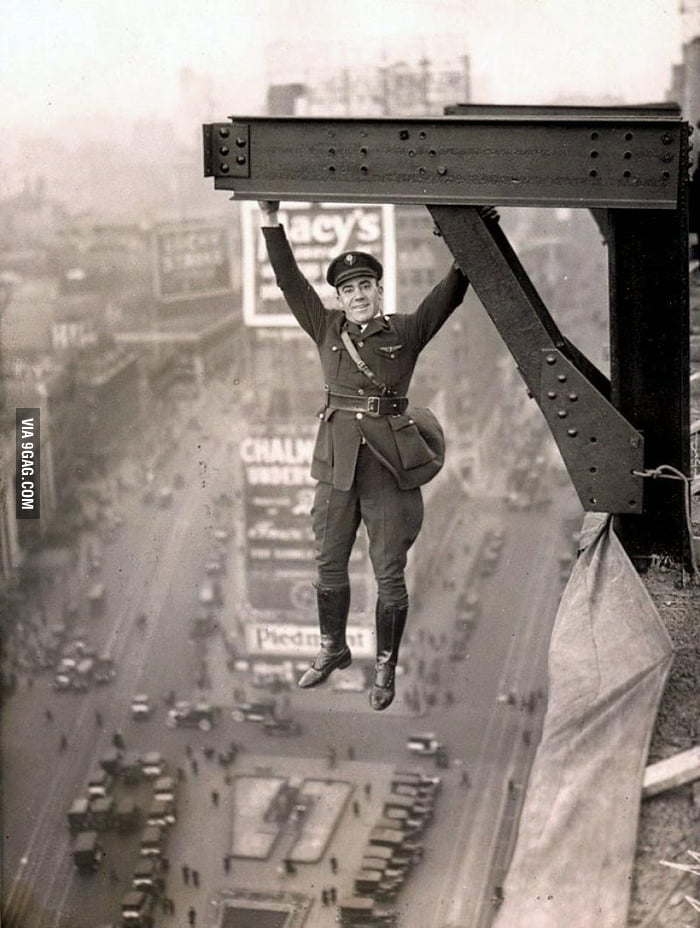 A member of New York police force hangs from a girder, 1920