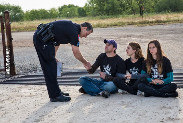 Police officer shakes hand of fracking protester before arresting him