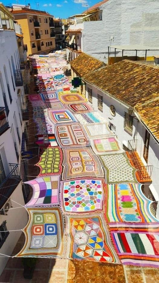 This is Malaga, Spain, where the women who lived there crocheted and put together this shadow-giving miracle. Below this is a pedestrian street with shops and cafés.