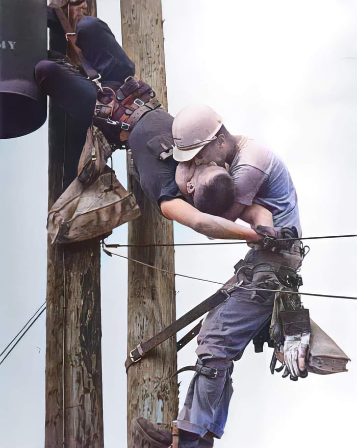 """Randall Champion accidentally touched a high-voltage line, electrifying himself and stopping his heart. A fellow linemen J.D. Thompson performed mouth-to-mouth CPR until paramedics arrived. Champion survived. This famous photo is known as """"The Kiss of Life."""" (1967)."""