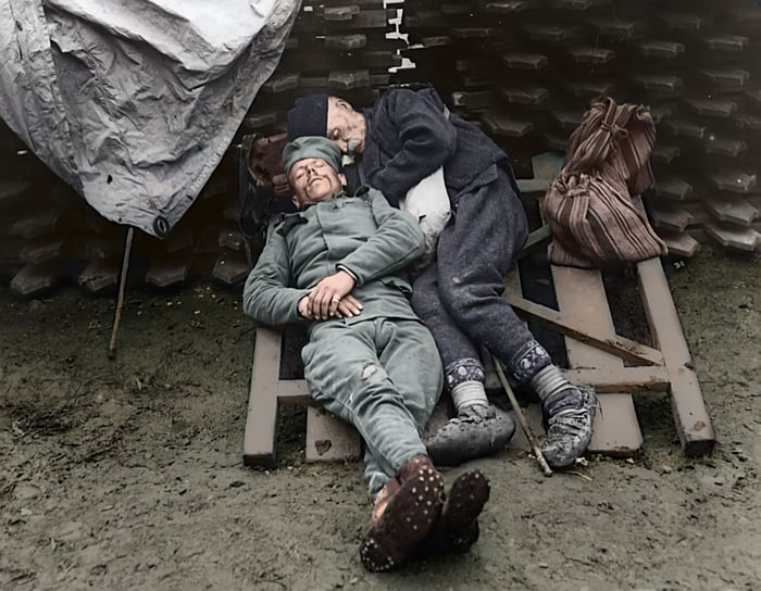 A Serbian soldier sleeps with his father who came to visit him on the front line near Belgrade, 1914