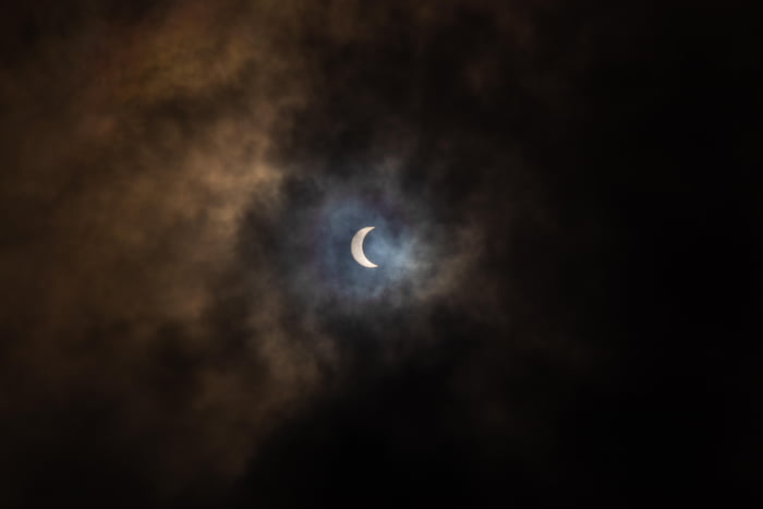 Partial solar eclipse today as seen from Kolkata, India. The monsoon clouds created an otherworldly halo, with tinges of blue, violent and green close to the sun, and yellow and orange outwards.